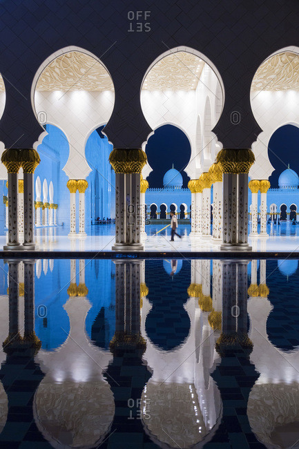 Abu Dhabi, United Arab Emirates - December 4, 2014: The arches and columns of Sheikh Zayed Mosque mirrored in water