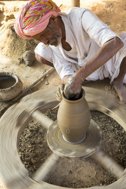 Udaipur, India - December 12, 2014: Man shaping a pot on wheel