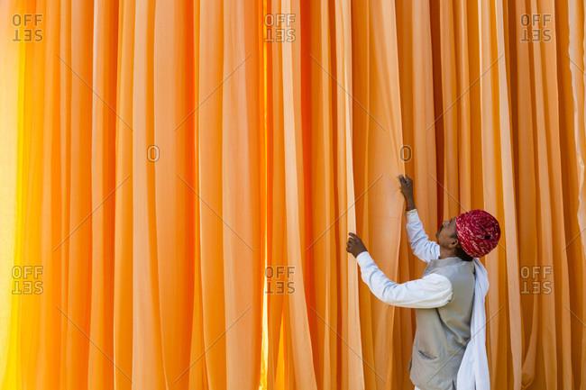 Man arranging orange textiles in a sari factory