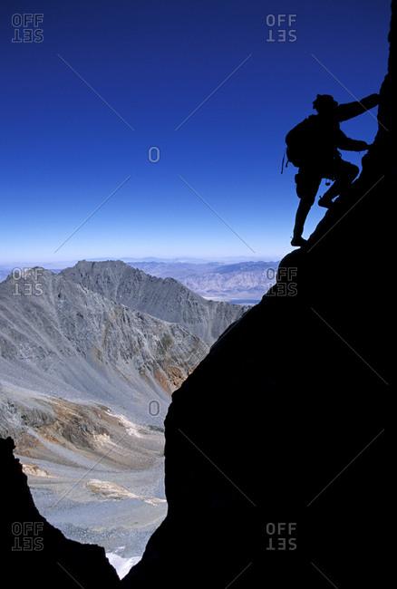 Man climbing at dawn on Split Mountain in the John Muir Wilderness, California