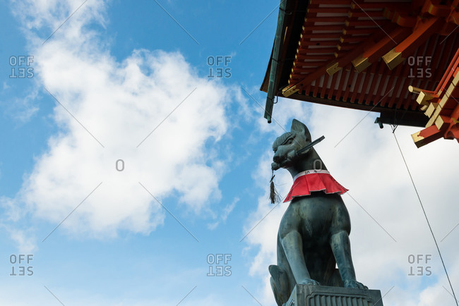Kyoto, Japan - January 17, 2015: Fox with a key in it's mouth at the gate of Fushimi Inari shrine, Kyoto, Japan