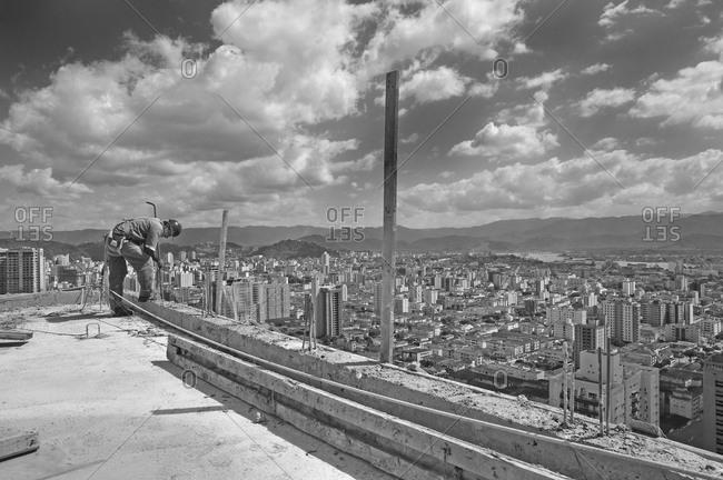 Santos, São Paulo, Sudeste, Brazil - October 8, 2010: A construction worker inserting a steel pole into concrete at a construction site in Sao Paulo, Brazil
