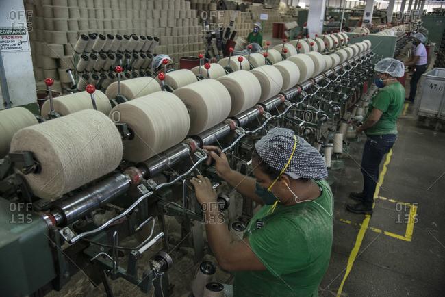 Manaus, Amazonas, Norte, Brazil - June 28, 2013: Women work at weaving machines in a jute processing plant