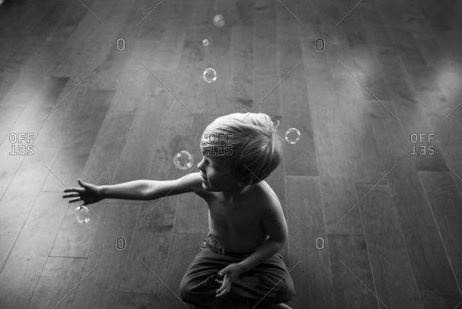 Young boy catching soap bubbles