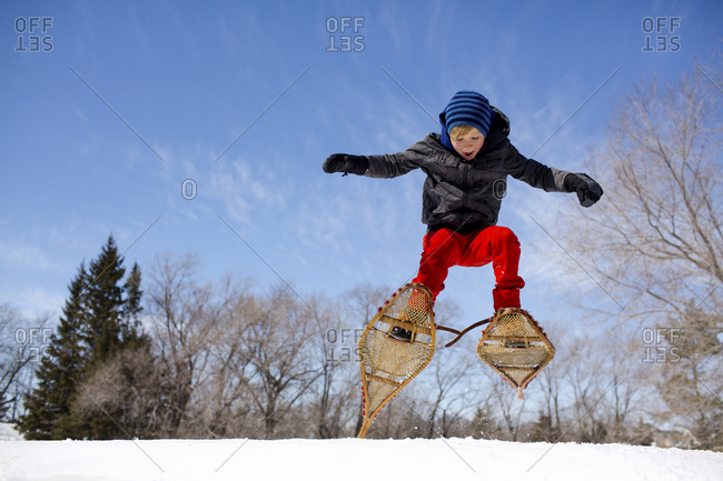 Enthusiastic boy jumps in the air while wearing snowshoes