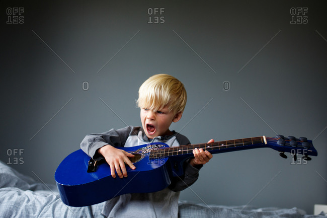 Young boy playing a blue guitar and singing