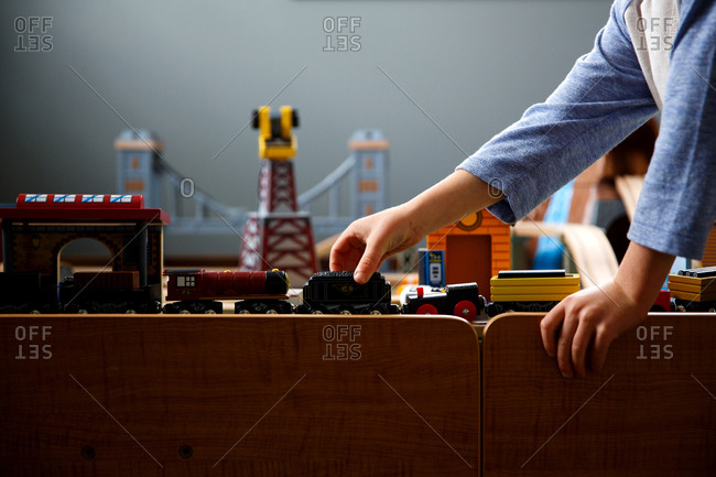 Boy plays with toy trains on a train table