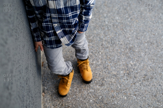 Chest-down shot of kid wearing work boots and plaid shirt
