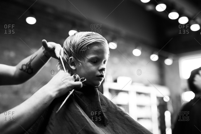 Young boy waits patiently while getting a hair cut