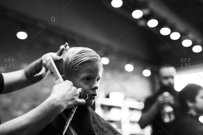 Boy watches in mirror while stylist cuts his hair