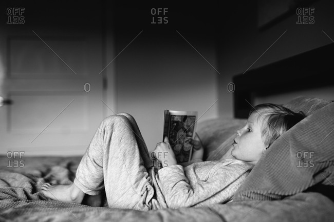 Young boy lying on a bed enjoying his book