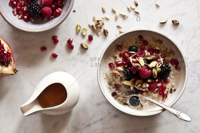 Bowl of fresh fruits and nut cereal with honey