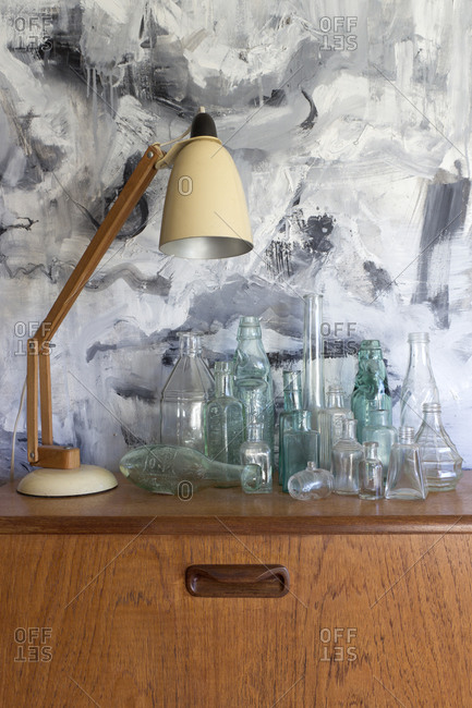 Swivel desk lamp and glass jars on side table