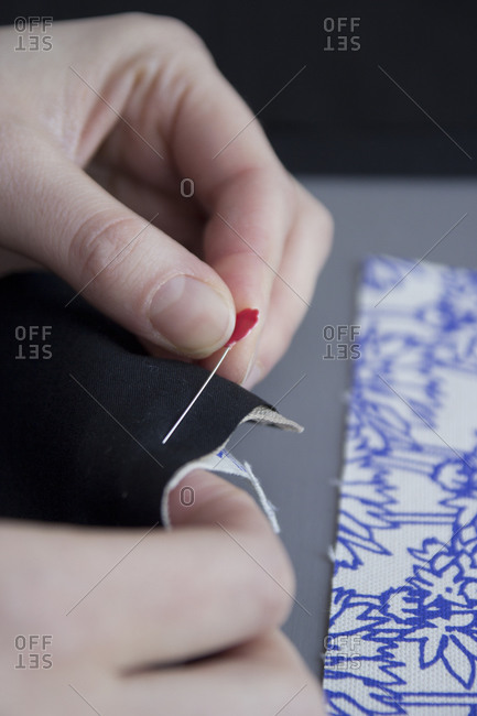 Woman pinning fabric seams together for sewing