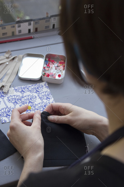 Woman pinning material seams together for sewing