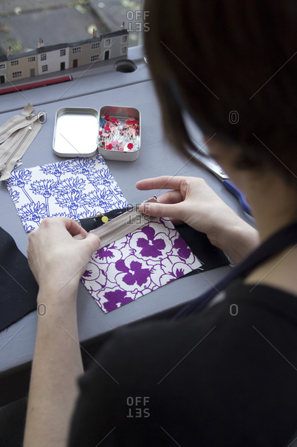 Woman laying zipper on fabric for sewing