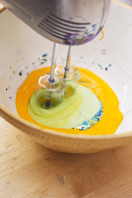 Various paint hues being mixed with electric mixer