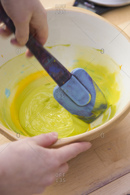 Person stirring bowl of paint with spatula
