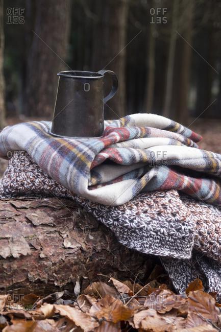 Metal mug on blanket pile in woods