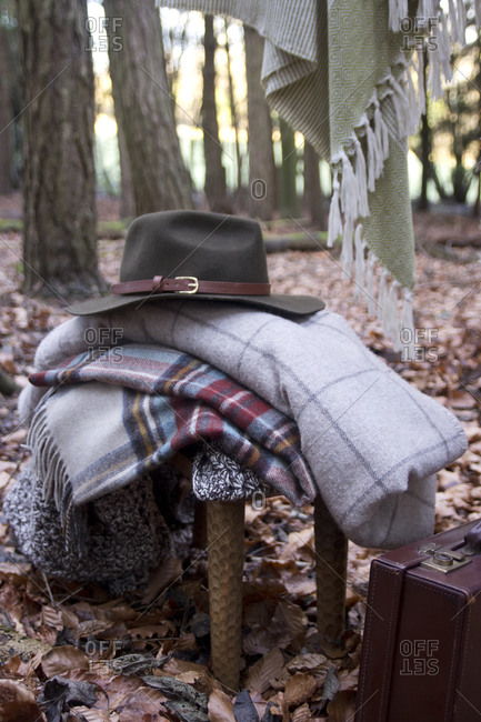 Fedora hat on blanket pile by briefcase in woods