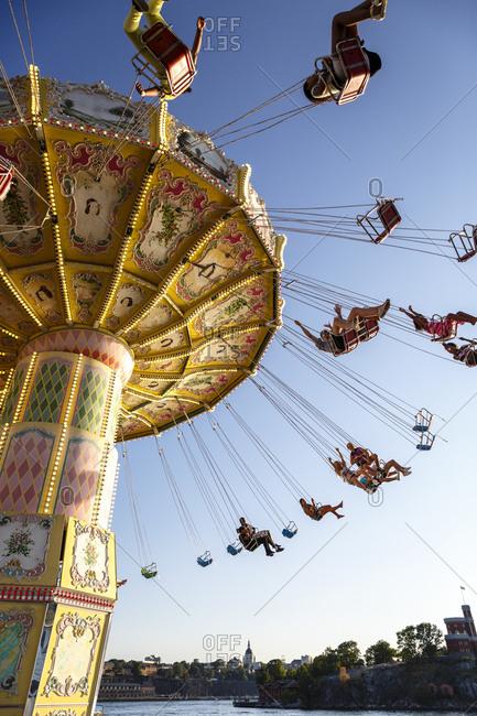 Stockholm, Sweden - July 25, 2014: Passengers ride the Kattingflygaren at Grona Lund amusement park in Stockholm