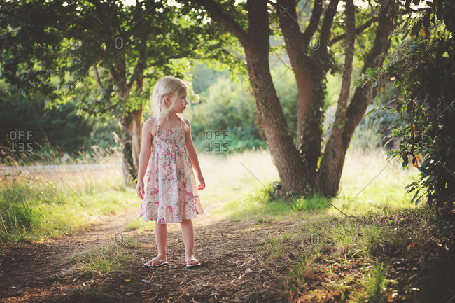 A little girl in a sundress turns around in a grassy field