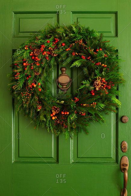 A holly and pine needle wreath on a green door