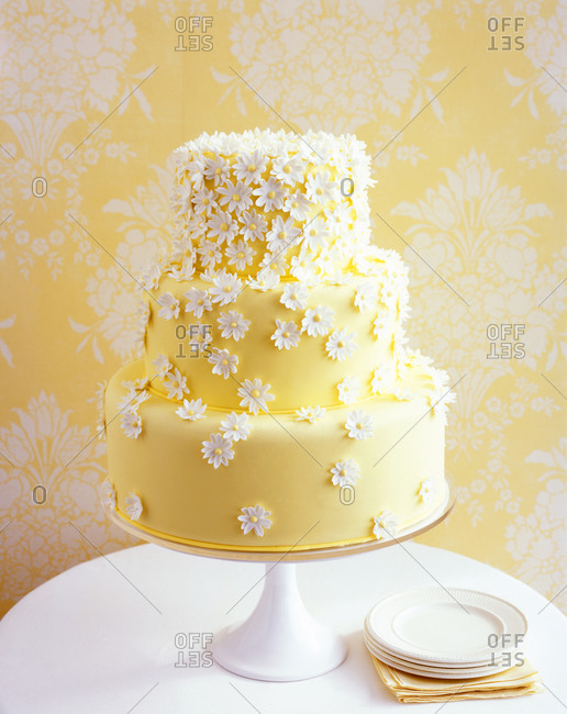 A yellow three-tiered wedding cake