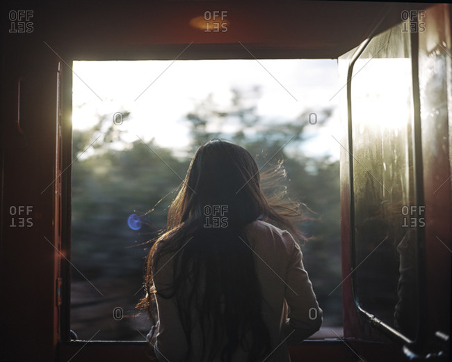 Back view of woman looking out the window of a train