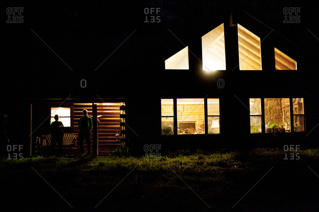Two people standing on the porch of their home at night