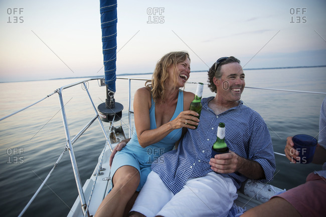 Friends laughing and drinking beer on a sail boat