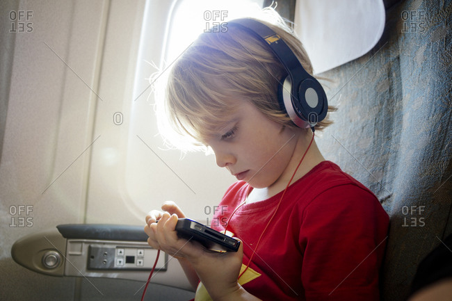 Young boy on an airplane occupies himself with smartphone