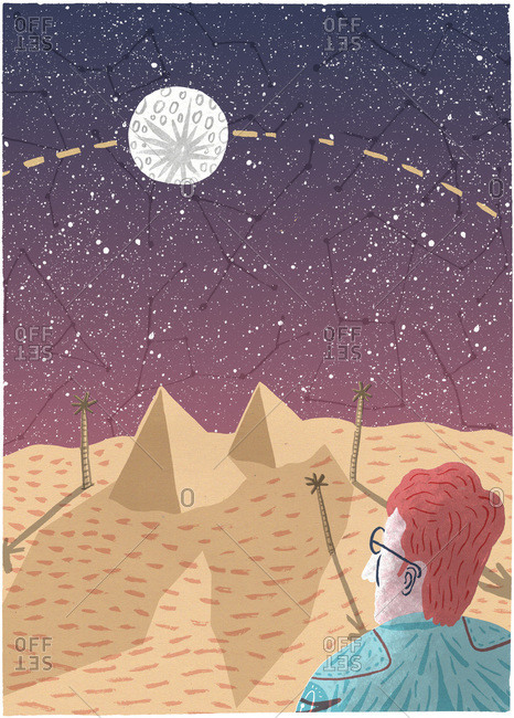 Man observing constellations above pyramids