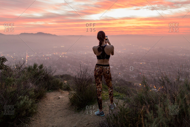 Young woman taking pictures from a hill at dusk