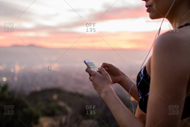 Young woman using her smartphone at sundown