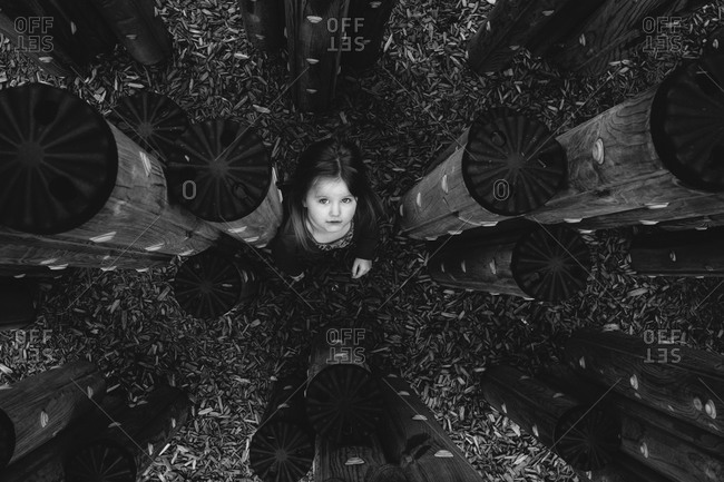 Young girl among playground pylons from above