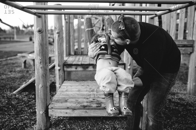A little girl and her dad playing on a jungle gym