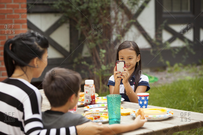 Girl taking picture of family at picnic table