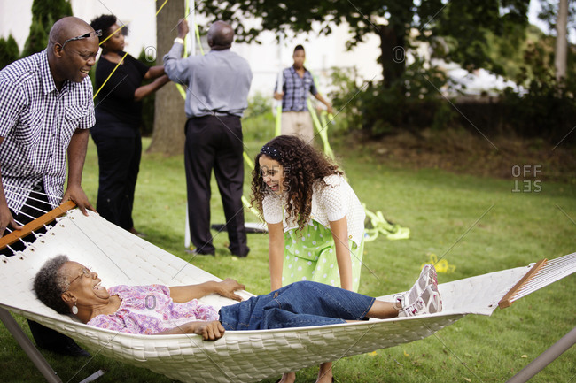 Grandmother lying on hammock during family reunion