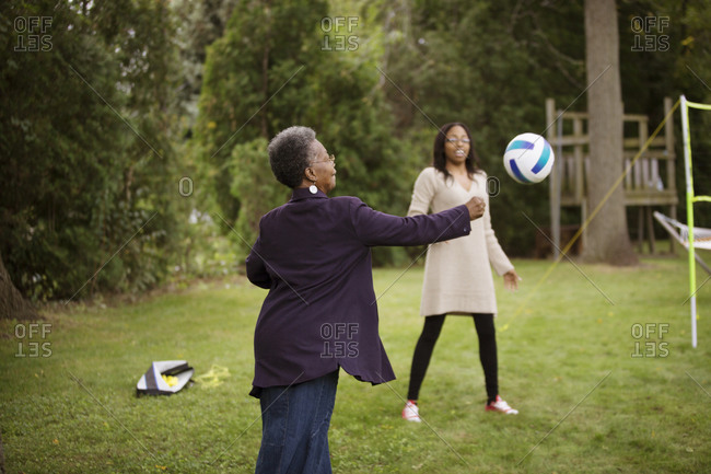 Grandmother and girl playing volleyball in yard