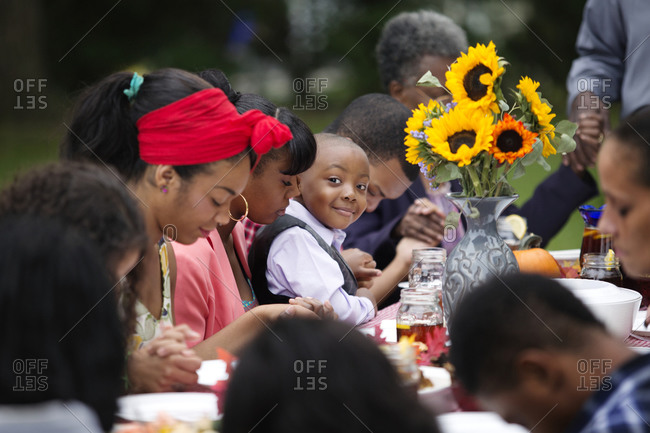 Young boy smiling during family prayer at dinner
