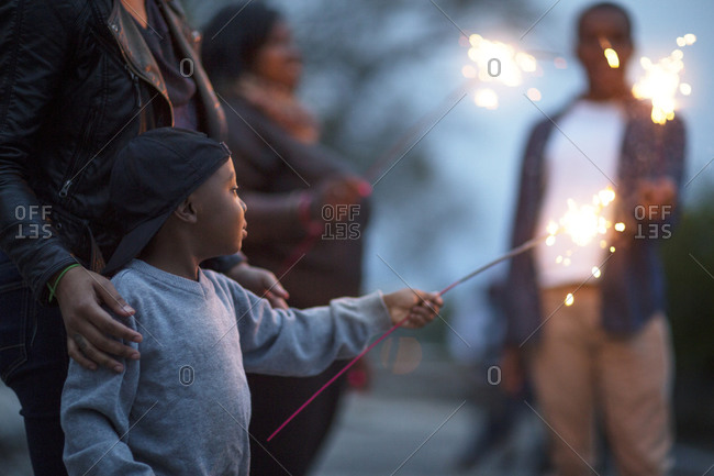 Family members holding sparklers at dusk
