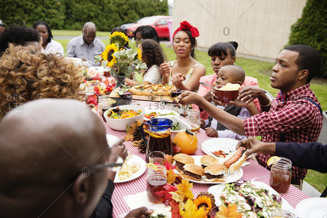 Family members sharing food across table