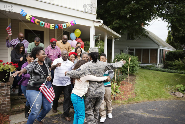 Family welcoming female soldier home with hugs