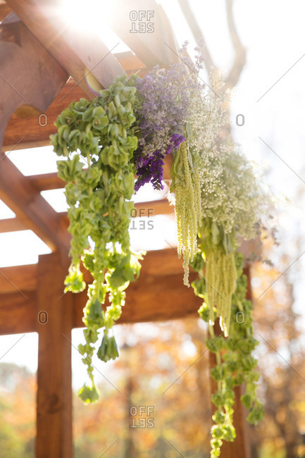 Flowers hang from wooden rafters at a wedding