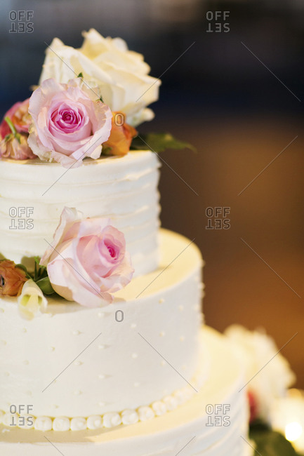A white wedding cake decorated with roses