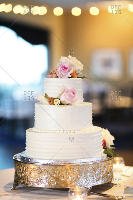 A white wedding cake on a silver cake stand