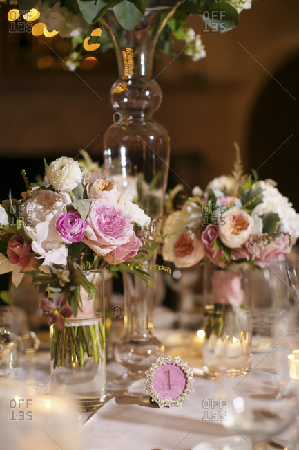 A dainty table number on a table set for a wedding reception