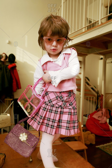 Young girl in home dressed up in skirt and purses