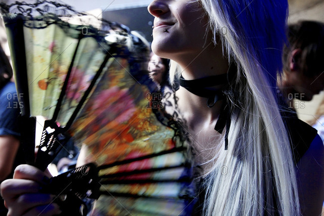 Close up of young woman with a fan at a nightclub in Milan, Italy